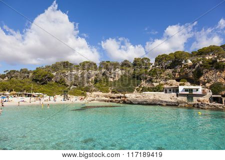 People enjoying beautiful beach with turquoise sea water in Mallorca island, Spain