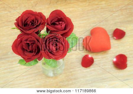 Red rosed on wood background.