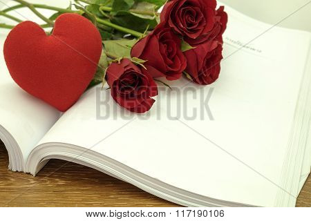 Red heart and rose flower with book on wood