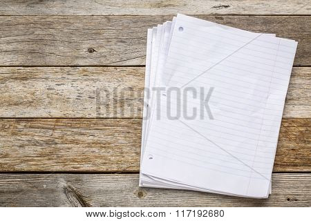 stack of blank notebook pages on a rustic, weathered wood background