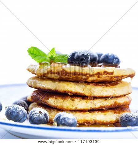 Pile Of Pancakes With Blueberries Sprinkled With Icing Sugar And Poured On With Honey