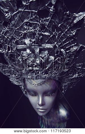Mannequin in metallic headwear with chains