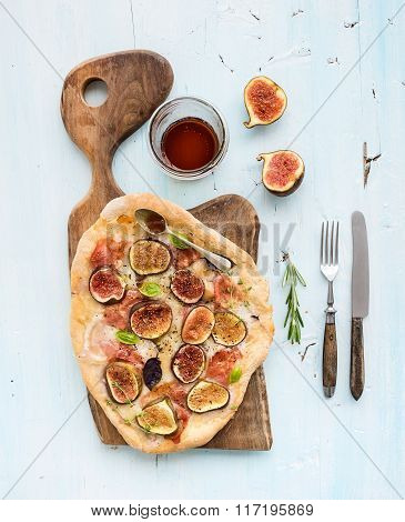Rustic homemade pizza with figs, prosciutto and mozzarella cheese on dark wooden serving board over