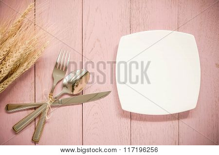 Cutlery Set: Knife, Fork And Spoons On Pink Wooden Background.