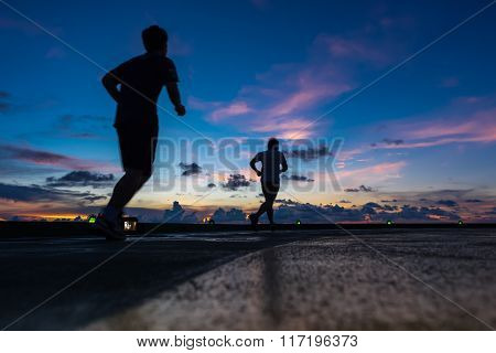 Two men running on oil and gas rig helipad in Gulf of Thailand in sunset time with helipad light on