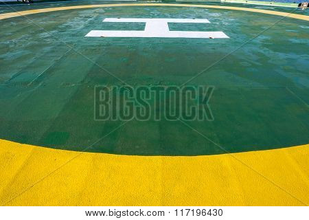 Green oil rig helipad with yellow circle line
