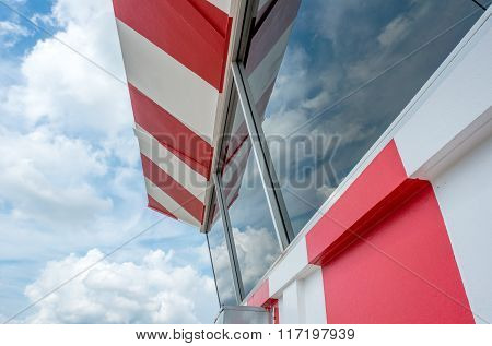 Air traffic control tower with red and white painted with scattered cloud and blue sky