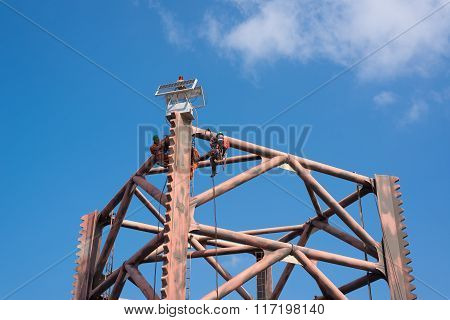 Men working at top of oil rig leg for painting