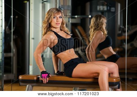 young fitness woman execute exercise on hip with exercise-machine Cable Crossover in gym