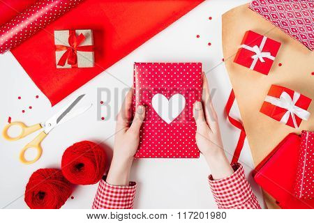 Female hands are wrapping a valentines gift on red