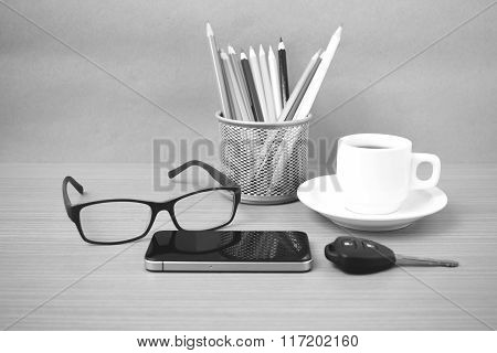 coffee phone eyeglasses color pencil and car key on wood table background black and white color
