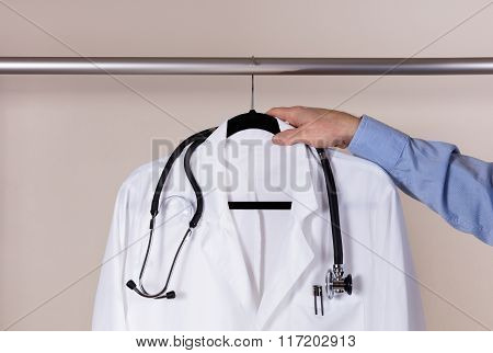 Medical White Consultation Coat With Stethoscope Being Taken Off Rack By Male Doctor Hand