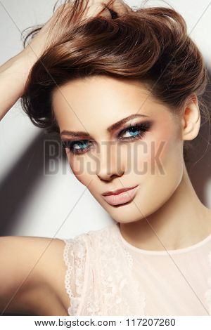 Portrait of young beautiful blue-eyed smiling woman with stylish make-up touching her hair