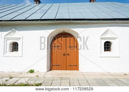 Old Wooden Orange Door In The Monastery Church.
