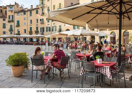 Lucca, Italy - September 14, 2015: Unidentified people eating traditional italian food in outdoor restaurant in city center of Lucca, Italy.