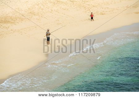 Java, Indonesia - April 11, 2015: Unknown fisherman with a boy with fishing rod on the beach on southern coast of Java, Indonesia