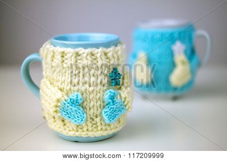 Two cups in sweater.