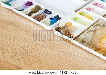 Plastic Artist Color Palette On Wooden Floor Art Concept