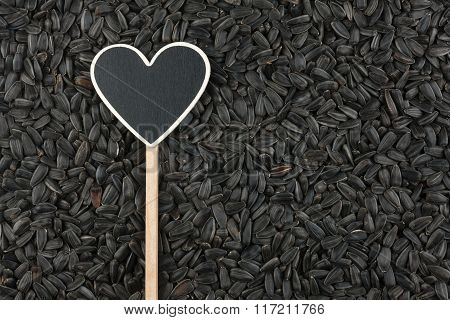 Pointer In The Form Of Heart Lies On Sunflower Seeds