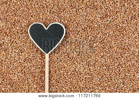 Pointer In The Form Of Heart Lies On Wheat Grains