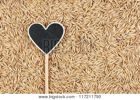 Pointer In The Form Of Heart Lies On Oats Grains
