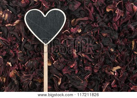 Pointer In The Form Of Heart Lies On Dried Hibiscus