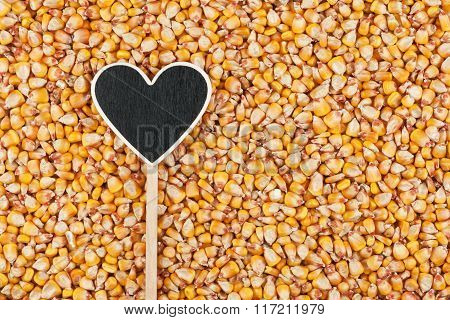 Pointer In The Form Of Heart Lies On Corn Grains