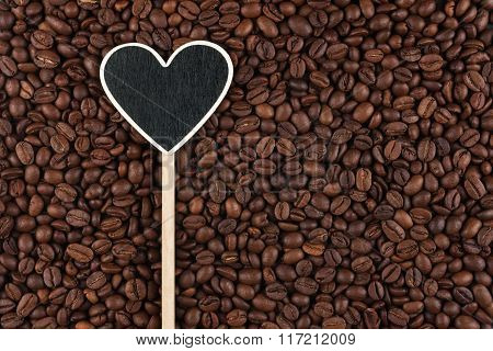 Pointer In The Form Of Heart Lies On Coffee Beans