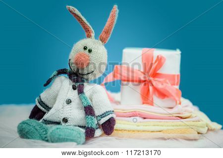 The baby clothes with a  white gift box