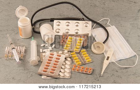 different medications, vials, syringe, thermometer, mask, stethoscope