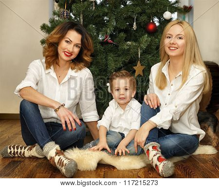 Beautiful Family Sitting Near Christmas Tree