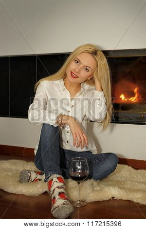 Beautiful Young Woman With Glass Of Wine Sitting Near Fireplace