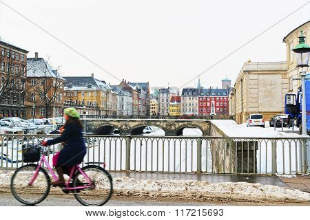 COPENHAGEN, DENMARK - JANUARY 5, 2011: Girl on bicycle passing by (in motion) the bridge of Copenhagen in winter. Copenhagen is the capital and most populated city in Denmark.
