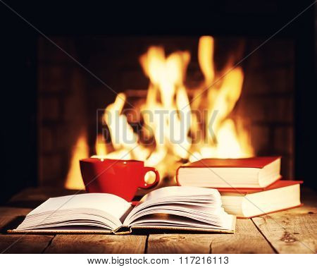 Red Cup Of Coffee Or Tea And Old Books On Wooden Table Near  Fireplace.
