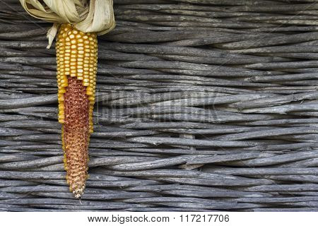 Ear Of Corn With Dry Leaves Against A Wooden Background