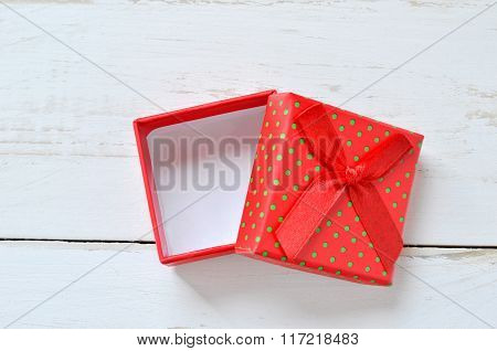 Red Gift Box Opened On Wooden Table