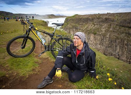 Happy biker on backdrop of waterfall in mountains Iceland