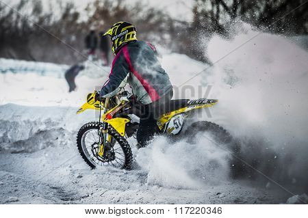 racer on a motorcycle rides in turn of wheels a spray of snow and mud