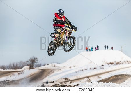 high jump motorcycle racer on snow covered hill