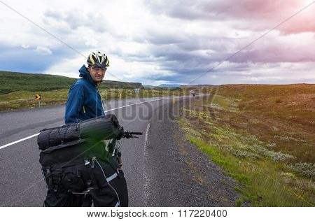 Biker rides on road at sunny summer day in Iceland. Travel and sport picture