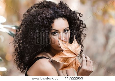 Young African Woman Siting On Bench In Park