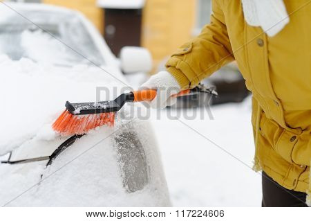 A Woman In Winter Removes Snow With The Car.