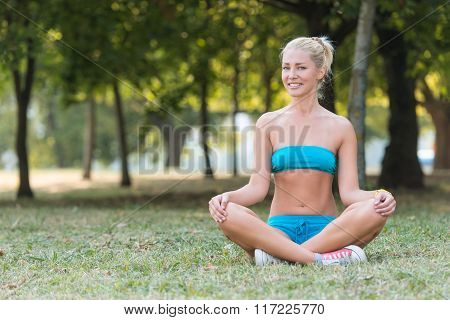 Smiling Woman During Yoga Exercises In The Park