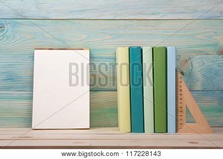 Back to school. Stack of colorful books on wooden table. Copy space