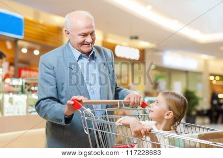 Happy grandfather and kid are shopping together.