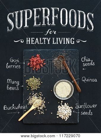 Superfoods on black chalkboard background: goji berries, chia, mung beans, buckwheat, quinoa, sunflo