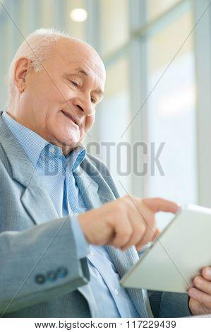 Shot of old man using digital tablet.