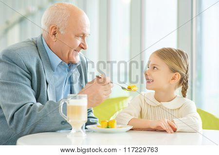 Grandfather asking granddaughter to try a pie.