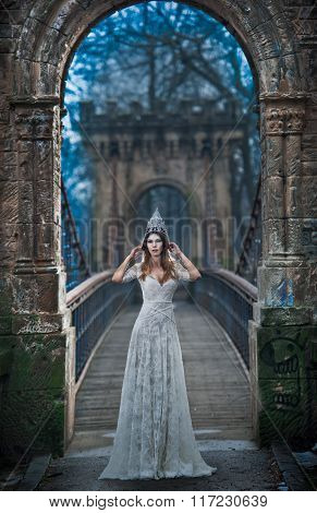 Lovely young lady wearing elegant white dress and silver tiara posing on ancient bridge