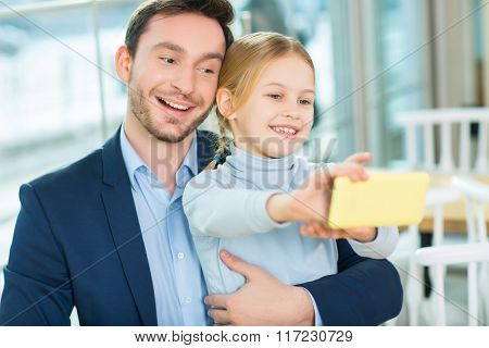 Smiling good-looking father with daughter posing for picture.